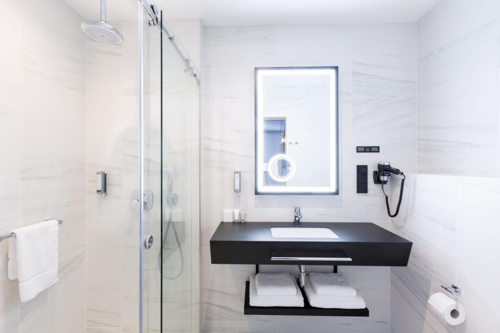 Mocnym akcentem kolorystycznym tej łazienki jest blat z wpuszczaną umywalką, wykonany z laminatu HPL. Fot. Abet Laminati
