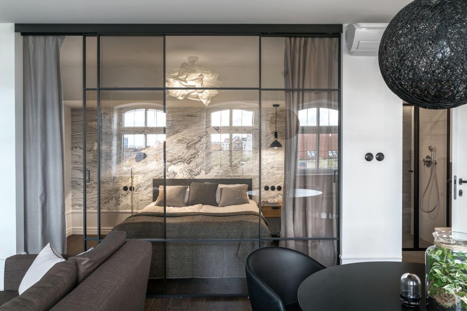 Dużym wyzwaniem było zaaranżowanie niewielkiej sypialni pozbawionej okna. Aby doświetlić jej wnętrze i uwolnić przestrzeń, architektki zdecydowały się na zastosowanie wielkoformatowych drzwi przesuwnych. Fot. Tom Kurek