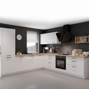 Czarne uchwyty dynamizują bryłę sterylnie białej zabudowy kuchennej. Fot. Kam