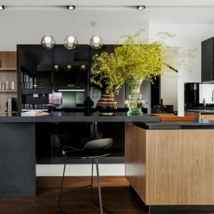 Czarne elementy użyty w zabudowie kuchennej (np. blat) dobrze komponują się z kolorami drewna. Fot. Zajc