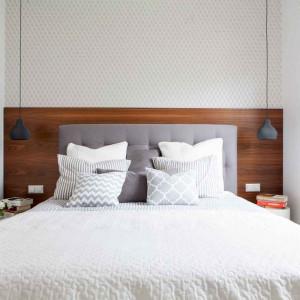 Tutaj zdecydowano się wyodrębnić z pomieszczenia garderobę, co znacznie uszczupliło powierzchnię sypialni. Króluje w niej łóżko z tapicerowanym zagłówkiem, stojące przy ścianie, obłożonej częściowo fornirowaną płytą. Po jego bokach zostało niewiele miejsca – wstawiono więc tam tylko niewielkie stoliki, na których nie zmieściłyby się lampki. Stąd pomysł na nisko zwijające lampy sufitowe. Ich światło nie razi w oczy osoby leżące w łóżku i jest odpowiednie do czytania. Projekt: Małgorzata Górska-Niwińska (Pracownia Architektoniczna MGN). Fot. Pracownia Architektoniczna MGN