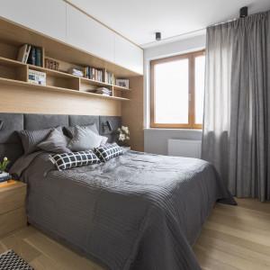 Gdy pomieszczenie jest niewielkie, na schowki warto wykorzystać wolne miejsce na ścianie, przy której stoi łóżko. Tak zrobiono tutaj. Nad szerokim, tapicerowanym wezgłowiem zbudowano półki, nad nimi, pod sufitem, szafki, a z boku, za szafką nocną – wąską szafę. Tym sposobem powstała wnęka, która po wyłożeniu drewnem wygląda bardzo zacisznie i przytulnie. Projekt: Małgorzata Górska-Niwińska (Pracownia Architektoniczna MGN). Fot. Pracownia Architektoniczna MGN