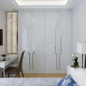 Ta sypialnia jest przykładem perfekcyjnie wykorzystanego miejsca. Jedną ze ścian zabudowano szafą, w którą wkomponowano  podświetlane półki ze szkła z przeznaczeniem na książki i dokumenty. Obok stoi lekkie biurko – to miejsce do pracy, a zarazem toaletka. Funkcjonalność to nie jedyna cecha tego pomieszczenia. Panuje w nim bowiem bardzo przytulny, zachęcający do odpoczynku klimat. Tworzą go dekoracyjne elementy wystroju – nastrojowe oświetlenie, miękkie tkaniny, srebrne wzory na frontach mebli i inne. Projekt: Małgorzata Górska-Niwińska (Pracownia Architektoniczna MGN). Fot. Yassen Hristov/ Hompics
