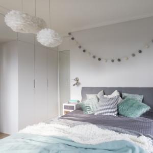 Nawet w oszczędnie urządzonym wnętrzu może panować miła atmosfera. Do tej funkcjonalnie urządzonej sypialni przytulność wprowadzają lampy z puchatymi abażurami, girlanda świetlna na ścianie i miękkie tkaniny na łóżku. Żeby zaoszczędzić miejsce na pojemne schowki, którymi zagospodarowano większą część bocznej ściany, zrezygnowano z tradycyjnych drzwi. Zastąpiono je suwanymi, chowającymi się za plecami szafy. Projekt: Małgorzata Górska-Niwińska (Pracownia Architektoniczna MGN). Fot. Pracownia Architektoniczna MGN