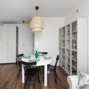Właściciele zdecydowali, że większość mebli w salonie – okrągły stół, który nie zabiera dużo miejsca oraz niski bufet – będą białe. Projekt: Clou Design. Fot. Clou Design