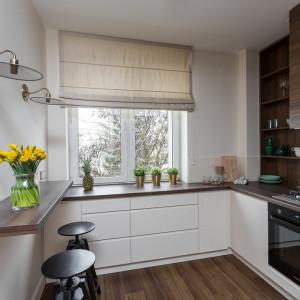 Architektkom udało się połączyć podłogę z egzotycznego drewna z blatami oraz frontami górnych szafek kuchennych. Projekt: Clou Design. Fot. Clou Design