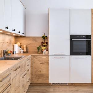 Podwójną kolorystykę mebli kuchennych z podziałem na górną i dolną zabudowę można dodatkowo zaakcentować dwoma typami uchwytów - delikatnymi, ale niezwykle dekoracyjnymi gałkami na górze i prostymi uchwytami w dolnej części zabudowy. Fot. Kam
