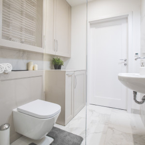 Szafki z dekoracyjnymi listwami na frontach wraz z imitującymi marmur płytkami na ścianach nadają łazience klasyczny charakter. W jednym ze schowków ukryto zbyt wyeksponowane grzejniki. Nie widać ich, ale ogrzewają pomieszczenie, bo w płycinie drzwiczek jest siatka, która nie zatrzymuje przepływu ciepła. Fot. Pracownia MGN