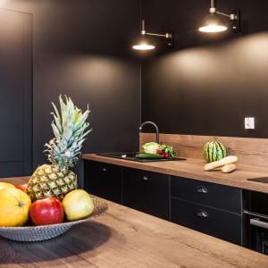 Utrzymane w ciemnych barwach matowe fronty mebli kuchennych i ściana tworzą spójną, jednolitą niemal powierzchnię, Fot. Kodo