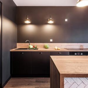 Szarości zastosowane w kuchni pozwalają ustalić optyczną granicę między pokojem dziennym i obszarem przygotowywania posiłków. Fot. Kodo