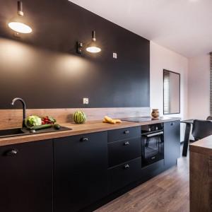 W kuchni dominują ciemne barwy, a całość aranżacji ożywia blask światła rzucanego przez lampy. Fot. Kodo