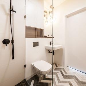 Motyw jodełki zastosowano także w projekcie łazienki, dzięki czemu współgra stylistycznie z pozostałą częścią mieszkania. Fot. Kodo