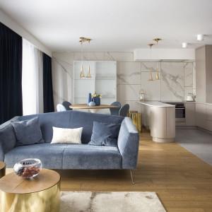 Szarobłękitna sofa dodaje lekkości wnętrzu. Projekt Pracownia Kaza