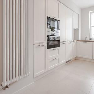 W prezentowanej kuchni dominującą barwę przełamuje wzór drewna, w postaci podłogi, blatów i półek, oraz szarość srebra i czerń, przewijające się w elementach, takich jak sprzęt AGD, oświetlenie, detale mebli czy akcesoria. Projekt: Kodo. Fot. Kodo