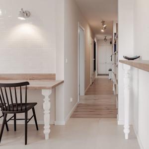 Przytulny charakter kuchni nadają dodatki – m.in. uchwyty i frezowane fronty wkomponowanych we wnękę szaf, tradycyjne w formie krzesła oraz stylizowane nogi stołu i cokołu. Projekt: Kodo. Fot. Kodo