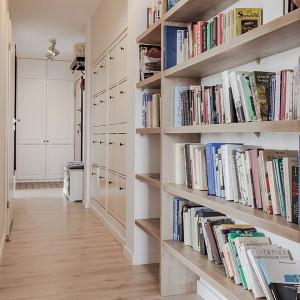 Zabudowa z motywem drewna nawiązuje do blatów i pełni funkcję pojemnej biblioteczki. Projekt: Kodo. Fot. Kodo