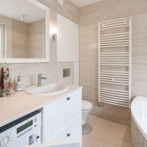 Spójność aranżacyjną utrzymano także w łazience – jasną ceramikę umieszczono w otoczeniu płytek w odcieniu ciepłego i przytulnego beżu. Projekt: Kodo. Fot. Kodo