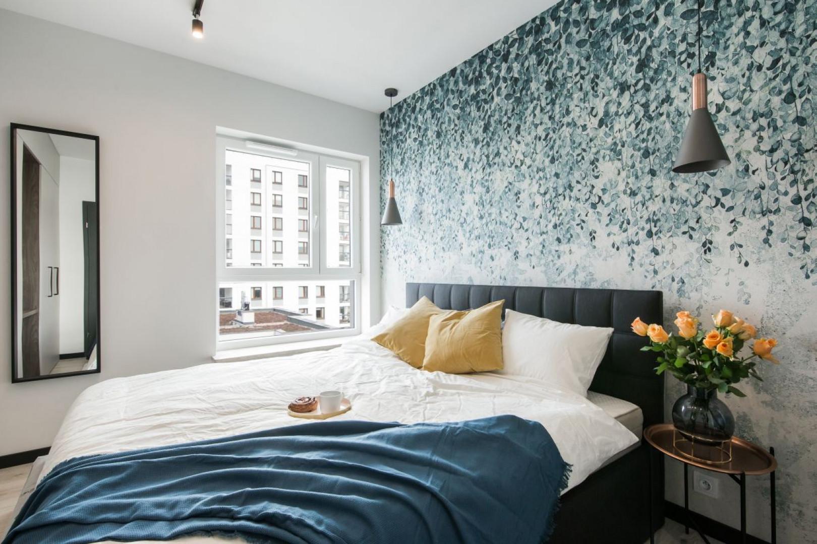 Motywem przewodnim tej aranżacji są pnącza w postaci przyciągającej wzrok tapety zdobiącej ścianę za łóżkiem. Fot. Kodo