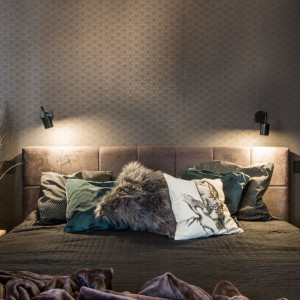 Łóżko umieszczono na tle ściany pokrytej ciemną tapetą z geometrycznym wzorem i uzupełniono o wyraziste dodatki – mięsiste poduszki oraz koc. Fot. Kodo