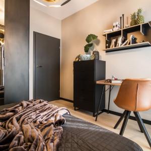 Naprzeciw łóżka zorganizowano eleganckie miejsce do pracy, wyposażone w niewielką komodę, proste biurko, półkę ścienną i krzesło. Fot. Kodo