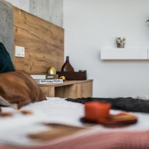 Zestawienie na jednej ścianie zimnego betonu i ciepłego drewna sprawia, że pomieszczenie jest jednocześnie surowe i przytulne. Fot. Kodo