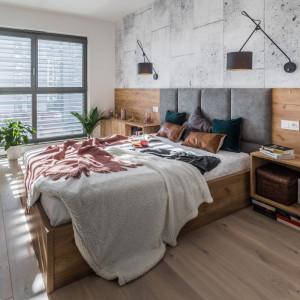Punktem centralnym w tak dużej przestrzeni jest obszerne łóżko z szarym, pikowanym zagłówkiem, wkomponowane w oryginalną zabudowę umieszczoną na całej długości ściany. Fot. Kodo