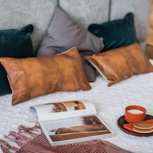 Minimalistyczny styl sypialni przełamują dodatki – wzorzysta narzuta, poduszki wykonane z aksamitnych, strukturalnych tkanin oraz tłoczonej skóry. Fot. Kodo