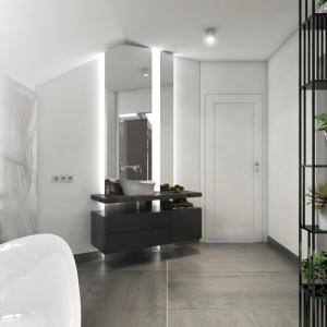 Miejsce przy drzwiach przeznaczono na umywalkę o takiej samej formie, co wanna. Wspiera się ona na kamiennym blacie. Pod nim – pojemna szafka na ręczniki i kosmetyki. Projekt: Małgorzata Górska-Niwińska. Fot. Pracownia Architektoniczna MGN