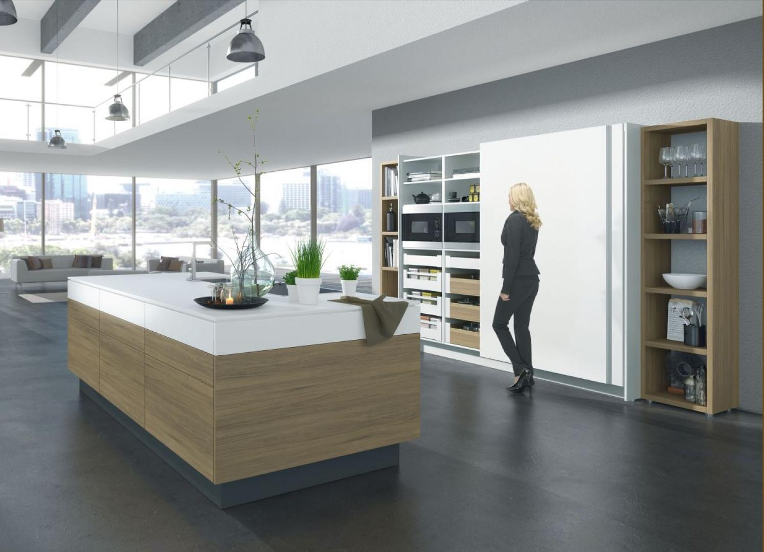 Dzięki systemom do drzwi przesuwnych możemy wygodnie kształtować przestrzeń otwartych wnętrz, udostępniając lub ukrywając strefę kuchenną. Fot. Hettich